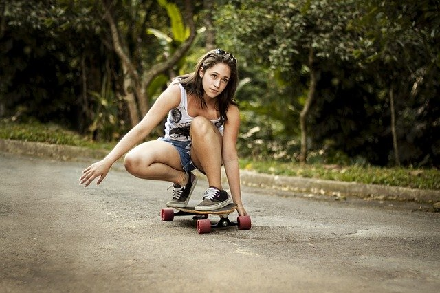 A young girl riding a skateboard up the side of a road