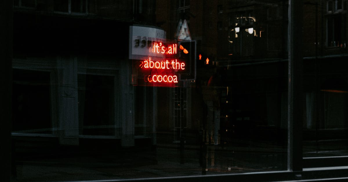 A sign in front of a building lit up at night