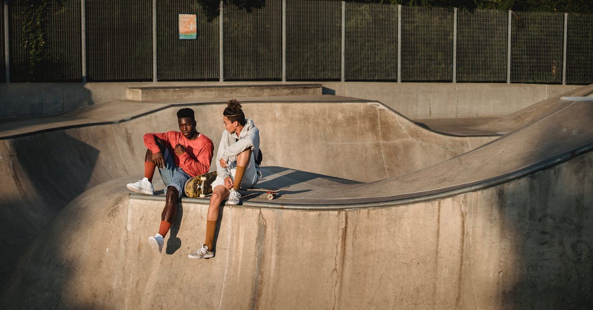 A young man riding a skateboard up the side of a ramp