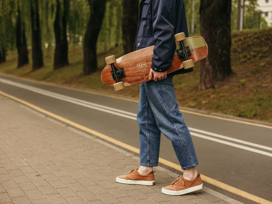 A man riding a skateboard up the side of a road