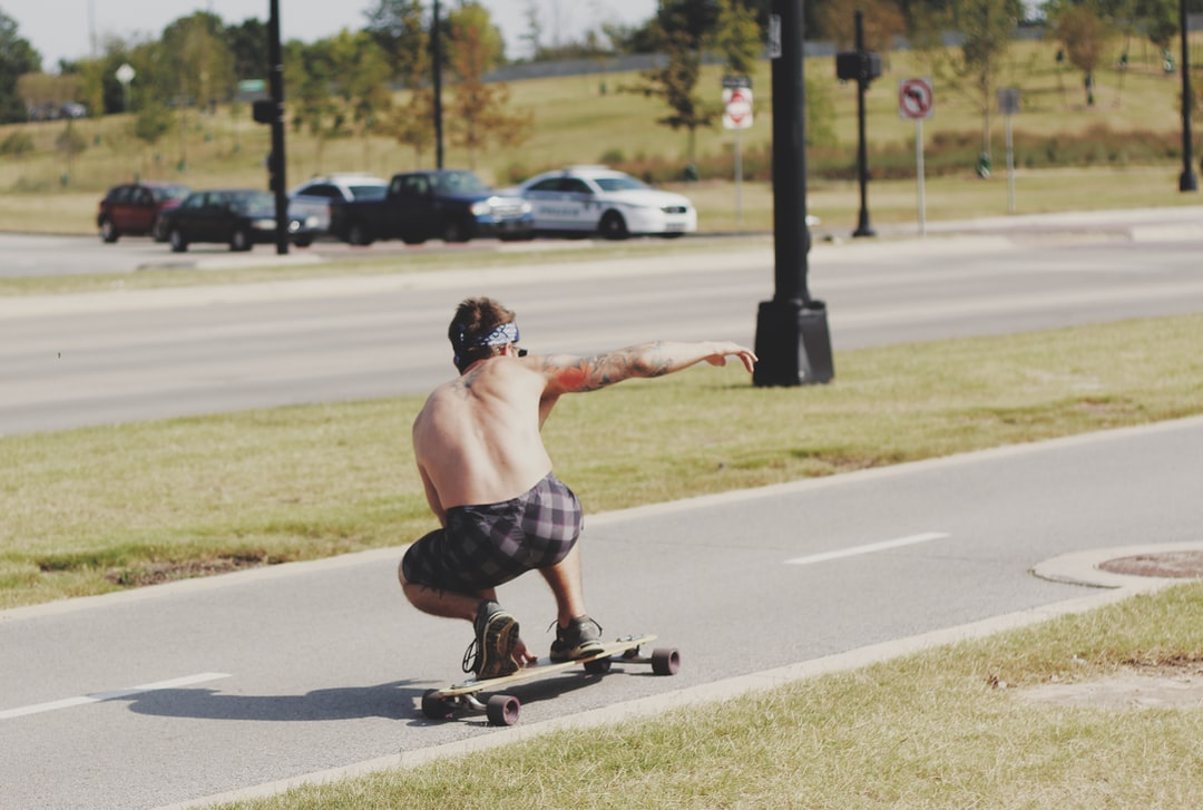 A person riding a skateboard down the side of a road
