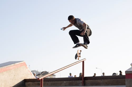 A man jumping in the air doing a trick on a skateboard